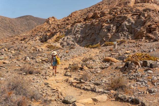 Een jonge vrouw loopt langs het pad van de canyon naar de mirador de la peñitas, westkust van het eiland fuerteventura, canarische eilanden. spanje