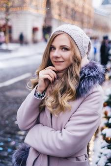 Een jonge vrouw loopt met kerstmis op het plein bij de versierde kerstbomen. candy is een lolly in de vorm van een hart.