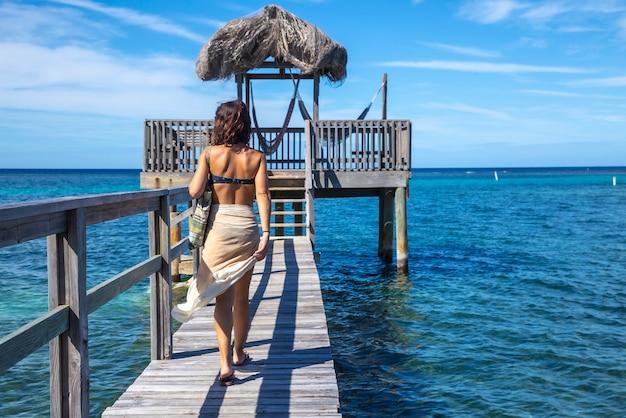 Een jonge vrouw loopt naar een houten constructie van de caribische zee op roatan island. honduras Premium Foto