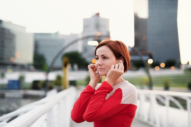 Een jonge vrouw loper met koptelefoon in de stad, rustend op de brug.