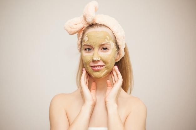 Een jonge vrouw maakt een gezichtsmasker van klei. cosmetische procedures. huidverzorging thuis.