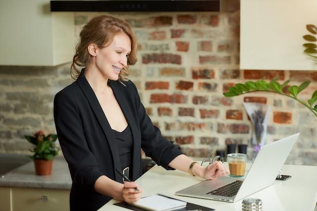 Een jonge vrouw met beugels werkt op afstand in haar keuken. een vrouwelijke baas die lacht op een videoconferentie met haar werknemers thuis.