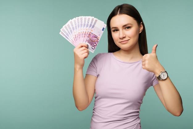 Een jonge vrouw met dollars in haar handen en duim toont omhoog geïsoleerd op blauw