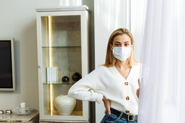 Een jonge vrouw met een beschermend masker staat bij het raam. zelfisolatieconcept, bescherming tegen coronavirus.