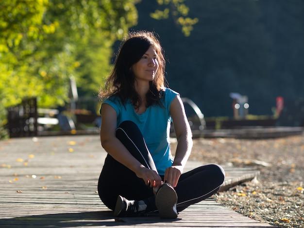 Een jonge vrouw met een blauw t-shirt zit op een loopband, 's ochtends joggen, uitrusten na het hardlopen.