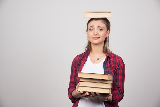 Een jonge vrouw met een boek op haar hoofd