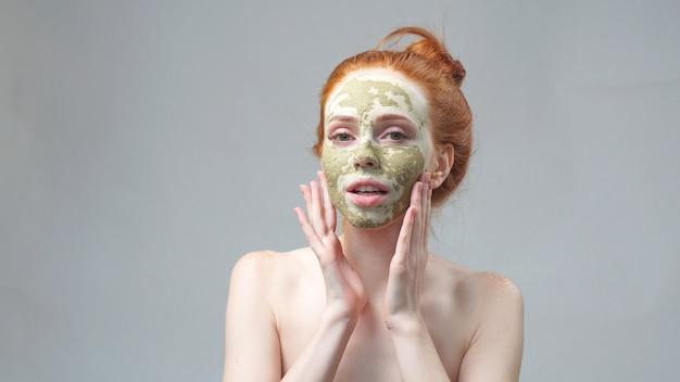 Een jonge vrouw met een groen droog moddermasker op haar gezicht op een geïsoleerde muur