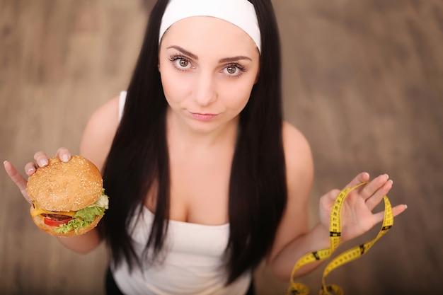 Een jonge vrouw met een hamburger en een meetlint. een meisje staat op een houten. het uitzicht vanaf de top. het van gezond eten.