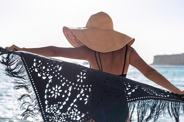 Een jonge vrouw met een hoed en een cape rust in de buurt van de zee.