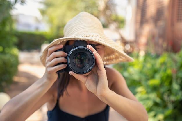 Een jonge vrouw met een hoed maakt foto's met een professionele slr-camera op een hete zomerdag