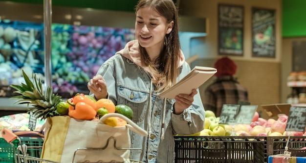 Een jonge vrouw met een laptop koopt boodschappen in de supermarkt.