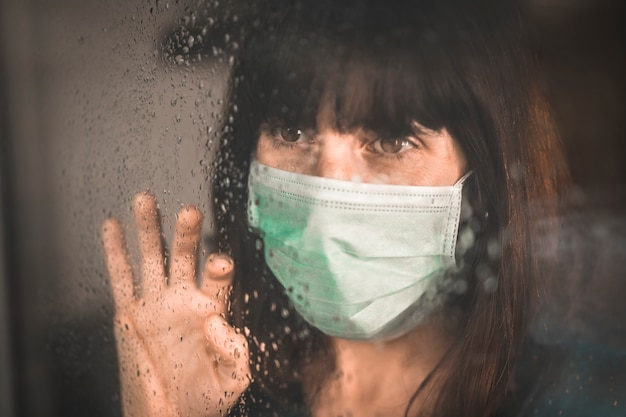 Een jonge vrouw met een masker in de covid-19 pandemie met haar hand op een raam en doorkijkend