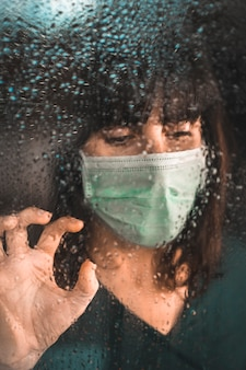 Een jonge vrouw met een masker in quarantaine van de covid-19 pandemie kijkt uit het raam op een regenachtige dag