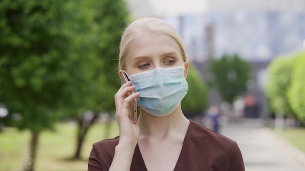 Een jonge vrouw met een medisch masker praat aan de telefoon op straat tegen de achtergrond van een grote stad. leven tijdens quarantaine en epidemie. 4k uhd