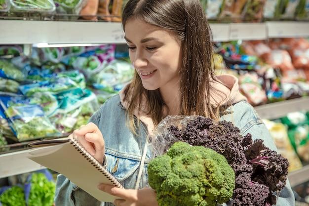 Een jonge vrouw met een notitieboekje koopt boodschappen in de supermarkt.