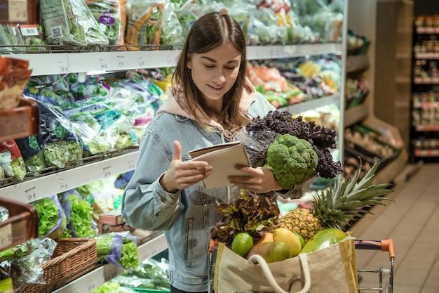 Een jonge vrouw met een notitieboekje koopt boodschappen in de supermarkt