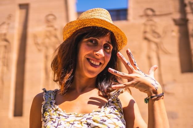 Een jonge vrouw met een nubische tatoeage van een zwarte edelsteen in de tempel van philae, een grieks-romeinse constructie, een tempel gewijd aan isis, de godin van de liefde. aswan. egyptische