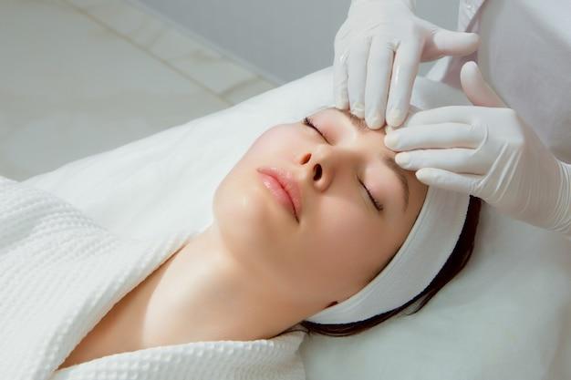 Een jonge vrouw met een perfecte huid krijgt een gezichtsmassage bij een cosmetische kliniek