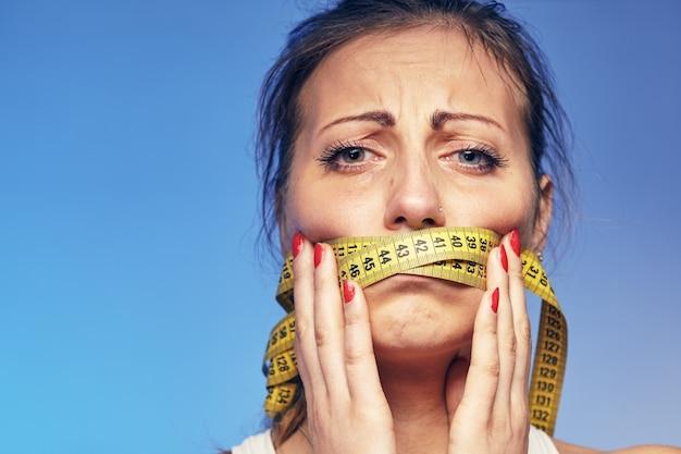 Een jonge vrouw met een plakband op de lippen. ze maakt zich zorgen over het dieet.