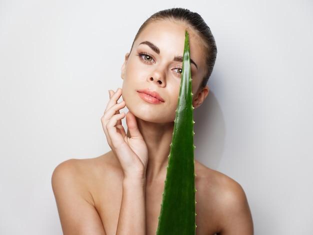 Een jonge vrouw met een schone huid en kapsels op haar hoofd houdt een aloëblad in haar hand