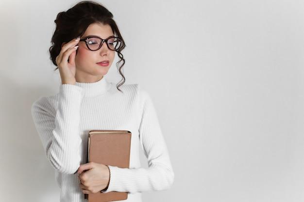 Een jonge vrouw met een slecht gezichtsvermogen met een bril loenst, een bril voor het gezichtsvermogen met dioptrie. verslechtering van het gezichtsvermogen. hoge kwaliteit foto