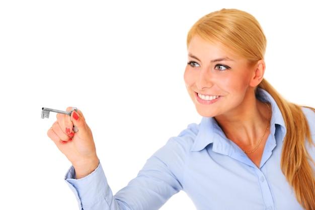 Een jonge vrouw met een sleutel op een witte achtergrond