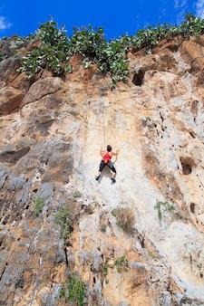 Een jonge vrouw met een touw bezig met de sporten van rotsklimmen op de rots.