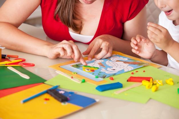 Een jonge vrouw met een zoon die pret het spelen in klei heeft