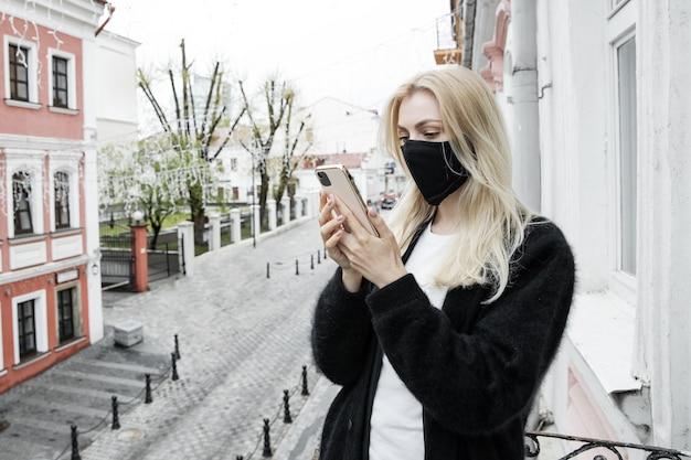 Een jonge vrouw met een zwart masker staat op het balkon van het kantoor en sms't aan de telefoon