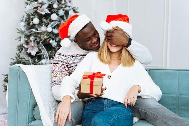 Een jonge vrouw met gesloten ogen kreeg een geschenk van een verrukte die haar omhelst. kerstmis en nieuwjaar concept. romantisch paar kerstcadeaus thuis uitwisselen.
