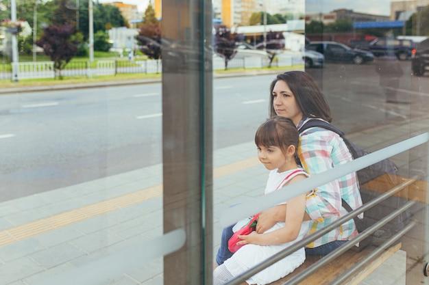 Een jonge vrouw met haar dochter wacht op een openbare bus bij het busstation