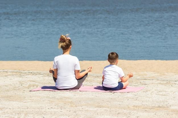 Een jonge vrouw met haar kind in witte t-shirts mediteert met haar vingers in een roze yogamat bij de zee