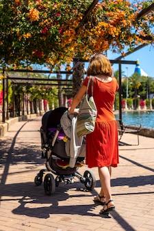 Een jonge vrouw met haar zoon in de auto die door het parque de las naciones in de stad torrevieja, alicante, middellandse zee loopt
