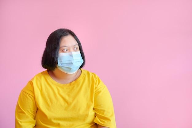 Een jonge vrouw met het syndroom van down draag een masker ter bescherming tegen het covid-19 coronavirus. ze is een studente hersenverlamming, het syndroom van down. ze droeg een gele jurk