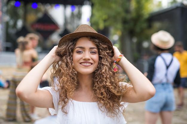 Een jonge vrouw met hoed op zomerfestival, camera kijken.