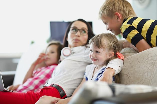 Een jonge vrouw met kinderen zit op de bank in de woonkamer en kijkt tv mama