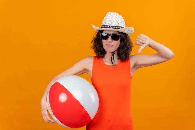 Een jonge vrouw met kort haar in een oranje overhemd dat zonnehoed en zonnebril draagt die opblaasbare bal houdt die duimen neer toont
