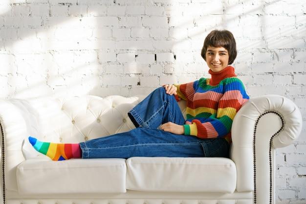 Een jonge vrouw met kort haar in een regenboogtrui en sokken zit op een witte bank, het concept van seksuele minderheden