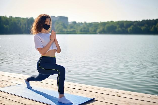 Een jonge vrouw met krullend haar dat yoga buiten doet
