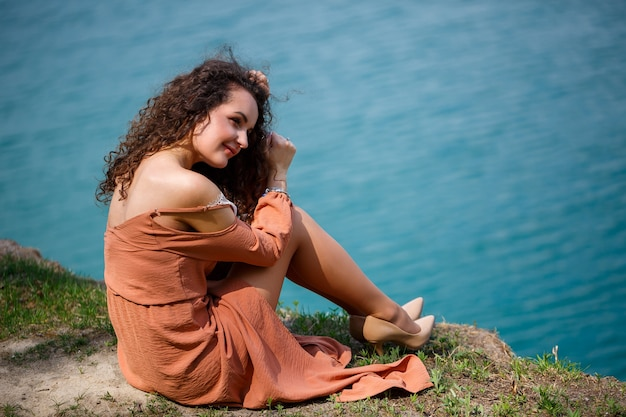Een jonge vrouw met krullend haar en een glimlach op haar gezicht zit in een groene weide op een achtergrond van blauw meer. warme zomerdag, gelukkig meisje, emoties van vreugde