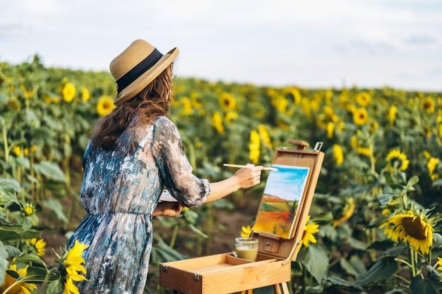 Een jonge vrouw met krullend haar en het dragen van een hoed schildert in de natuur. een vrouw staat in een zonnebloem veld op een mooie dag