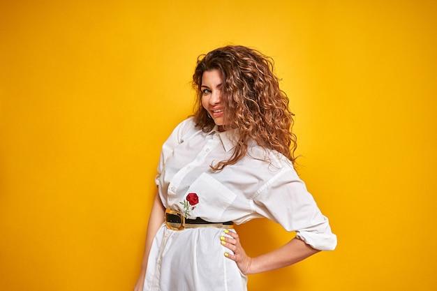 Een jonge vrouw met krullend haar in een wit overhemd staat met haar hand op haar zij, kijkt voor zich uit en glimlacht met haar hoofd schuin.