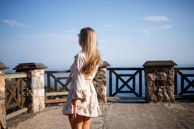 Een jonge vrouw met lang blond haar in een top en een rok loopt op een zonnige zomerdag. gelukkig meisje met een glimlach op haar gezicht en in zonnebril loopt op een zonnige dag Premium Foto