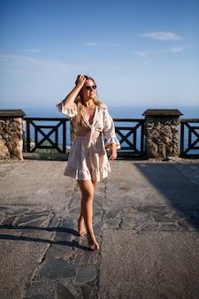 Een jonge vrouw met lang blond haar in een top en een rok loopt op een zonnige zomerdag. gelukkig meisje met een glimlach op haar gezicht en in zonnebril loopt op een zonnige dag