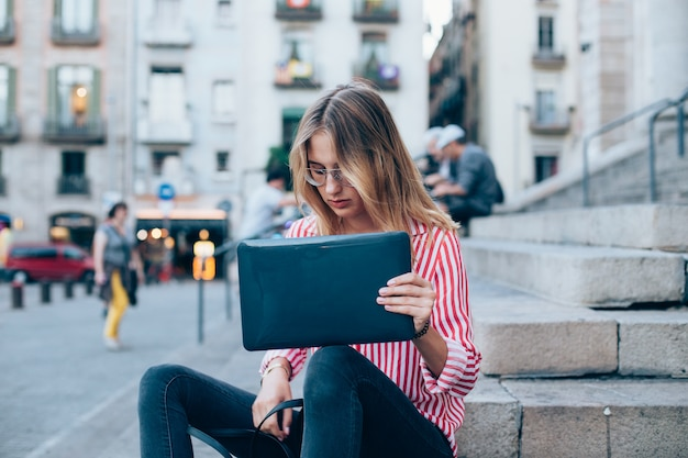 Een jonge vrouw met laptop zittend op de trap, vlakbij de universiteit