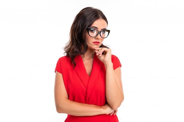 Een jonge vrouw met lichte make-up, in een rode zomerjurk, staat met een bril op en denkt aan iets serieus