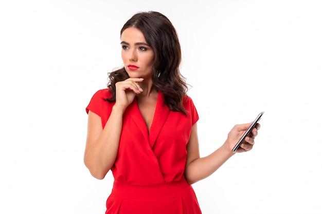 Een jonge vrouw met lichte make-up, in een rode zomerjurk, staat met een telefoon in de hand en denkt aan iets