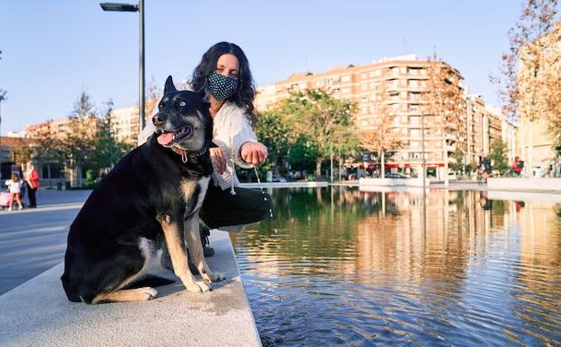 Een jonge vrouw met masker zit in een parkfontein met haar hond. nieuw normaal. vriendschap van het dier met de vrouw