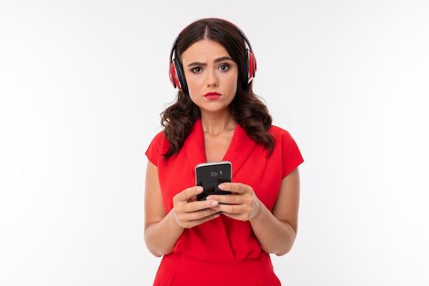 Een jonge vrouw met rode lippen, lichte make-up, donker golvend lang haar, in een rood pak, zwarte bril met transparante bril staat en luistert naar muziek in een koptelefoon, houdt de telefoon in zijn handen