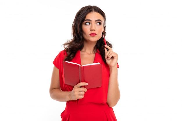 Een jonge vrouw met rode lippen, lichte make-up, een oogverblindende glimlach, donker golvend lang haar, in een rode zomerjurk, houdt een notitieboekje vast en denkt na